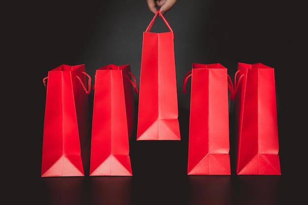 Mão escolhendo o saco de compras de papel vermelho com fundo preto
