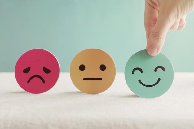 Mão escolhendo rosto feliz