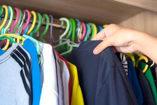 Mão escolhendo roupas para vestir no guarda-roupa.