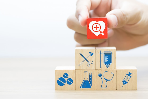 Mão escolher bloco de madeira com ícone de medicina e saúde.