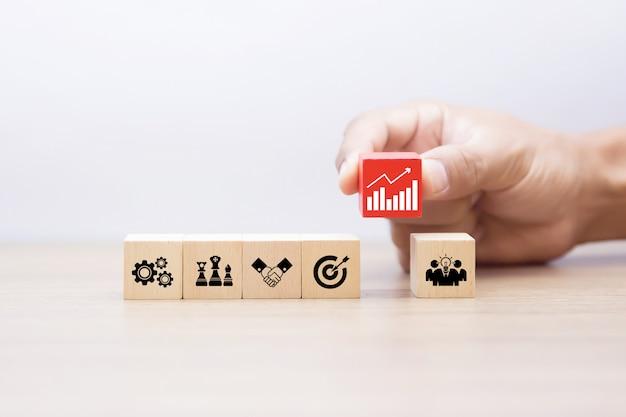 Mão escolher blog de madeira com ícones de gráfico de negócios