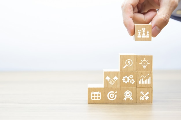 Mão escolher blog de madeira com ícones de negócios