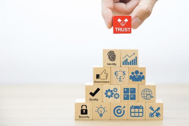 Mão escolher ícones de confiança no bloco de brinquedo de madeira.