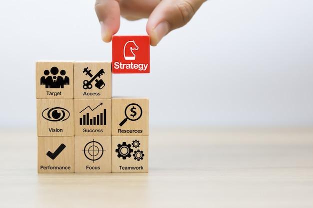 Mão escolher ícones de estratégia de negócios no bloco de brinquedo de madeira.