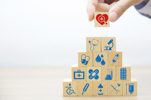 Mão escolher ícones de medicina e saúde no bloco de madeira.
