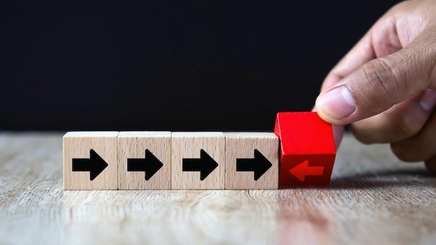 Mão escolher o ícone de seta no bloco de madeira apontando para direções opostas.