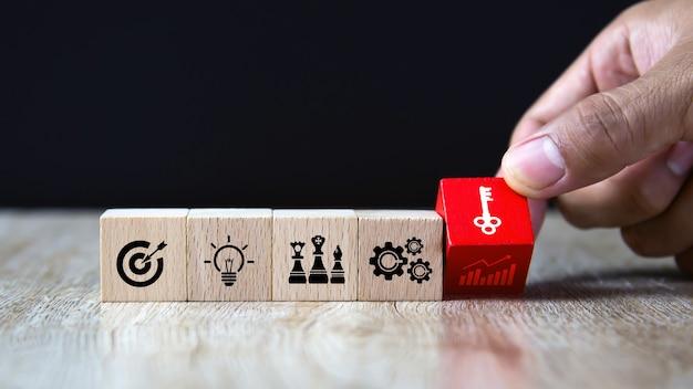 Mão escolher pilha de blocos de madeira com a chave no ícone de estratégia de negócios.