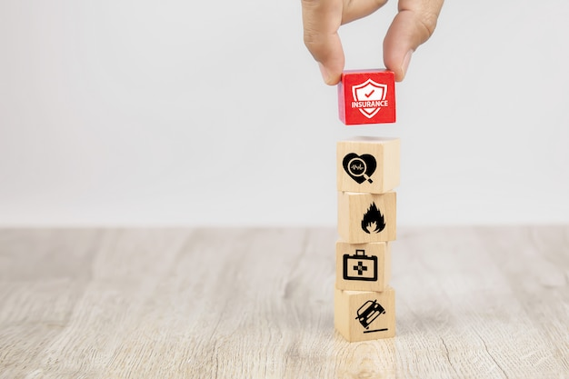 Mão escolher um cubo de blocos de brinquedo de madeira com proteger o ícone de seguro.