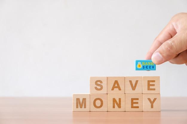 Mão escolhida com símbolo de moeda e cubo de madeira com palavra economizar dinheiro.