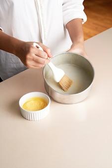Mão escovar manteiga dentro da bandeja de bolo