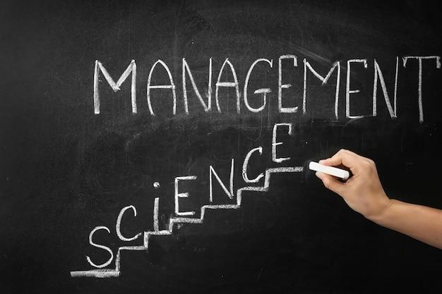 Mão escrevendo a frase gestão ciência no quadro-negro