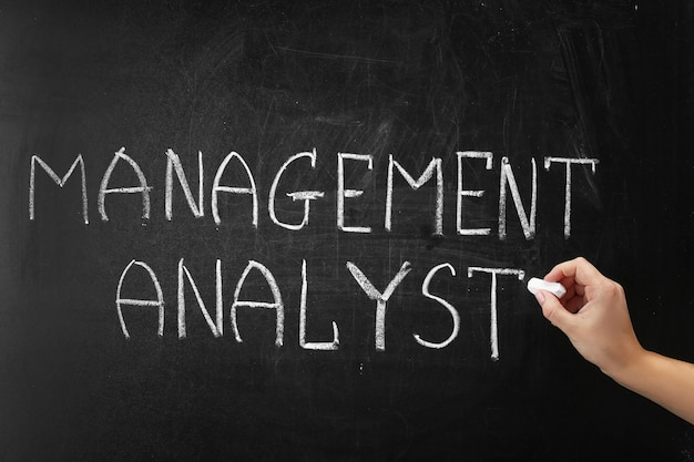 Mão escrevendo a frase management analyst no quadro-negro
