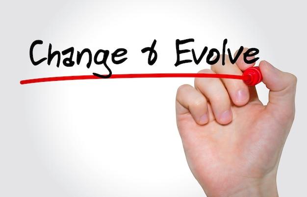 Mão escrevendo a inscrição change and evolve com marcador, conceito