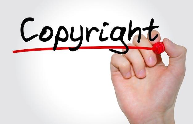 Mão escrevendo a inscrição de direitos autorais com marcador