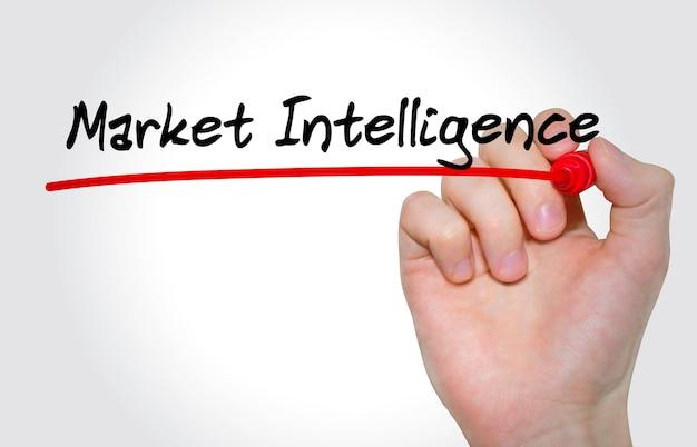 Mão escrevendo a inscrição market intelligence com marcador, conceito