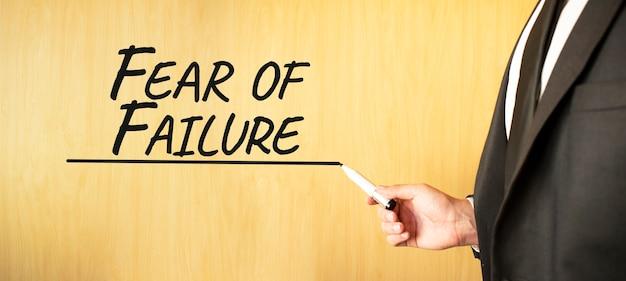 Mão escrevendo a inscrição medo de fracasso, com marcador, conceito de negócio