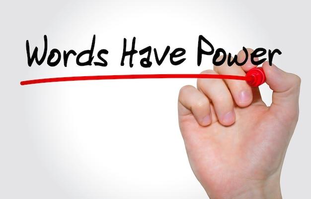 Mão escrevendo a inscrição palavras têm poder com marcador, conceito