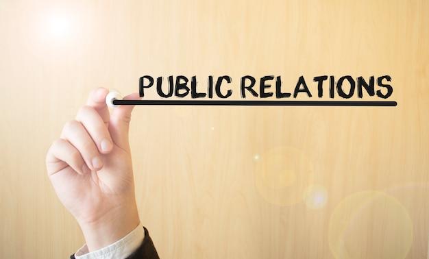 Mão escrevendo a inscrição relações públicas, com marcador, conceito de negócio