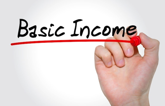 Mão escrevendo a inscrição renda básica com marcador, conceito