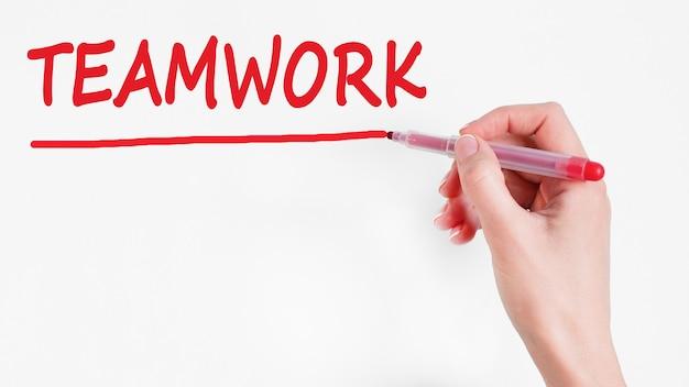 Mão escrevendo a inscrição trabalho em equipe com marcador vermelho, conceito,