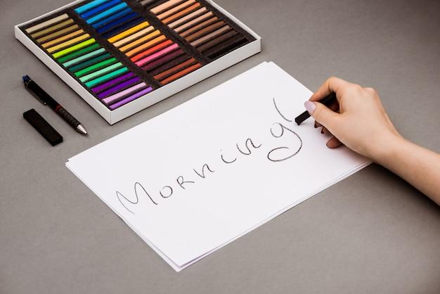 Mão escrevendo a palavra manhã no papel com giz de cera pastel
