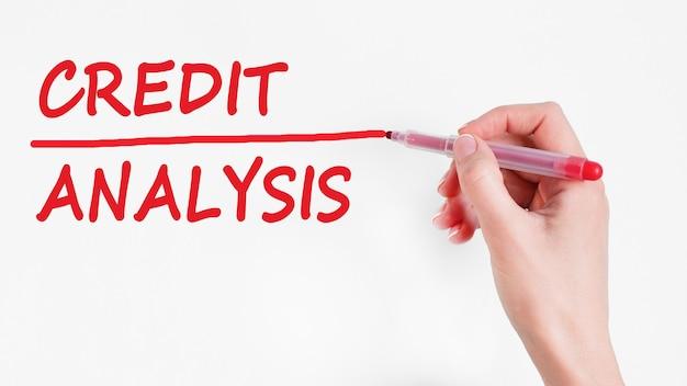 Mão escrevendo análise de crédito de inscrição com marcador de cor vermelha, conceito, imagem de estoque.