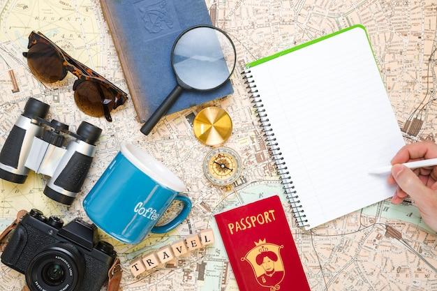Mão escrevendo ao lado de elementos de viagem