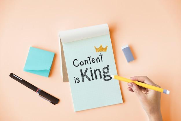 Mão escrevendo conteúdo é rei em um bloco de notas