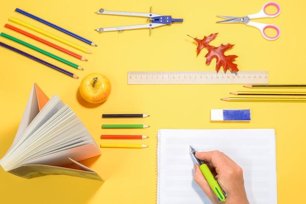Mão escrevendo em um caderno sobre uma mesa com material escolar