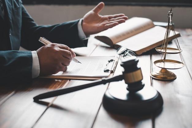 Mão escrevendo em um livro com elementos de juiz em uma mesa