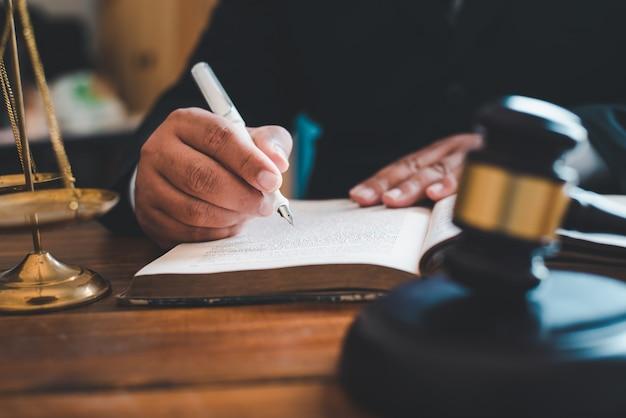 Mão escrevendo em um livro com o macete do juiz