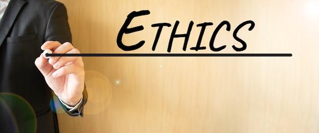 Mão escrevendo ética de inscrição, com marcador, conceito de negócio