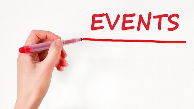 Mão escrevendo eventos de inscrição com marcador, conceito, imagem conservada em estoque