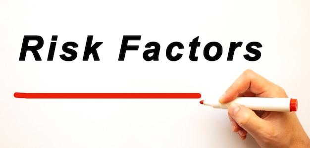 Mão escrevendo fatores de risco com marcador vermelho. isolado no fundo branco. conceito de negócios.