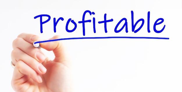 Mão escrevendo inscrição lucrativa com marcador de cor azul, conceito, imagem conservada em estoque. avise-me quando quiser reservar uma consultoria de investimentos.