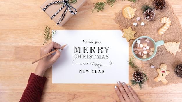 Mão escrevendo inverno cartão postal natal e feliz ano novo e chocolate quente com marshmallow