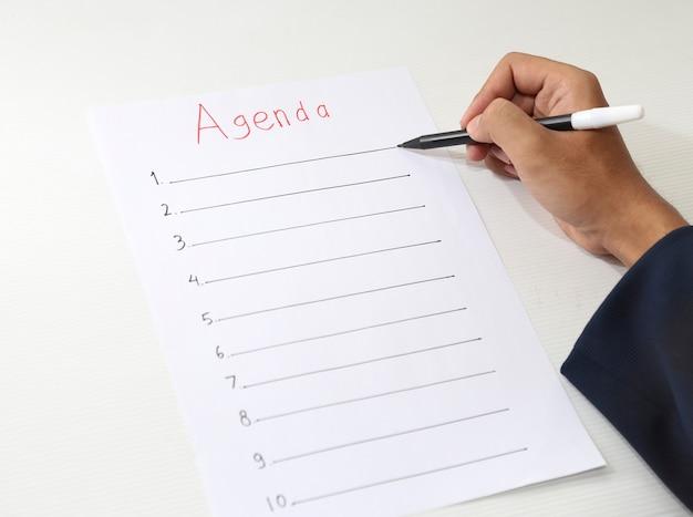 Mão escrevendo lista de agenda de negócios
