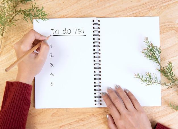 Mão escrevendo maquete postal para fazer a lista e chocolate quente com marshmallow na mesa de madeira