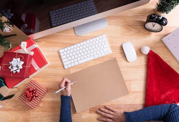 Mão escrevendo mock-se cartão de feliz natal e feliz com decoração de natal na área de trabalho.