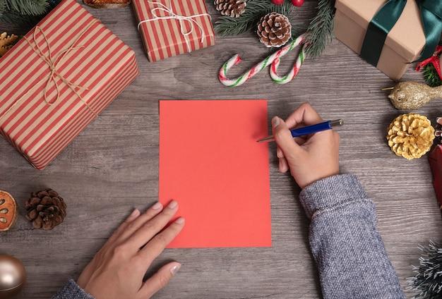 Mão escrevendo mock-se cartão de feliz natal e feliz com decoração de natal na mesa de madeira.
