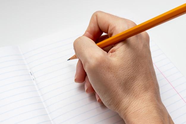 Mão escrevendo na folha branca alinhada de notebook com um lápis amarelo