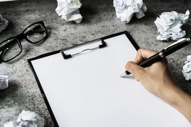 Mão escrevendo na pasta de arquivo com bolas de papel amassado no escritório de turismo, conceito de problemas de criatividade