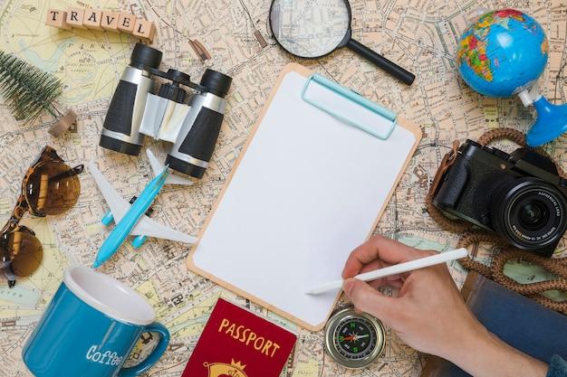 Mão escrevendo na pasta rodeada por elementos de viagem