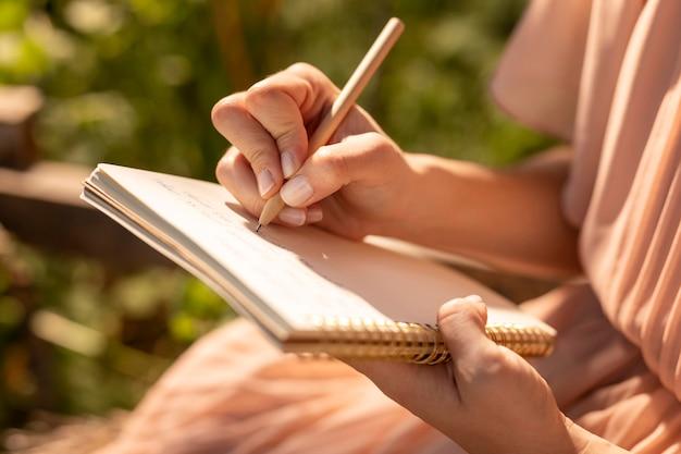 Mão escrevendo no caderno de perto