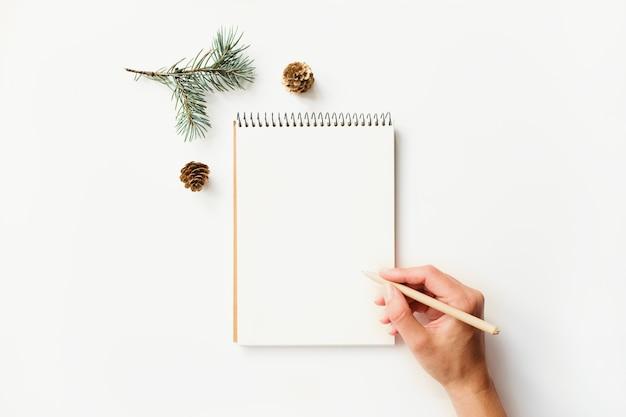 Mão escrevendo no caderno e no ramo de abeto com pinhas
