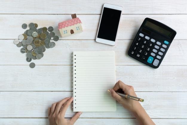 Mão escrevendo no caderno, modelo de casa, moedas e calculadora planos de poupança para habitação conceito financeiro, cópia espaço, vista superior