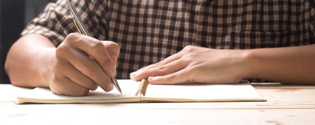 Mão escrevendo no caderno, poema e idéia documento quase