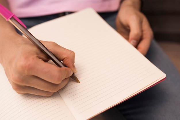 Mão escrevendo no caderno