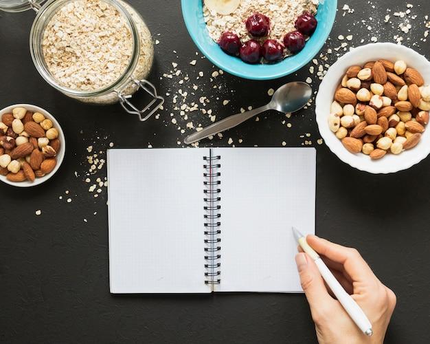 Mão escrevendo no notebook perto de mistura de nozes e aveia jar