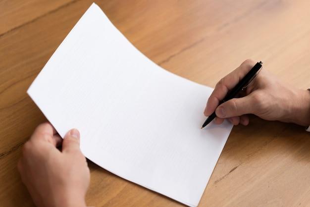 Mão escrevendo no papel vazio